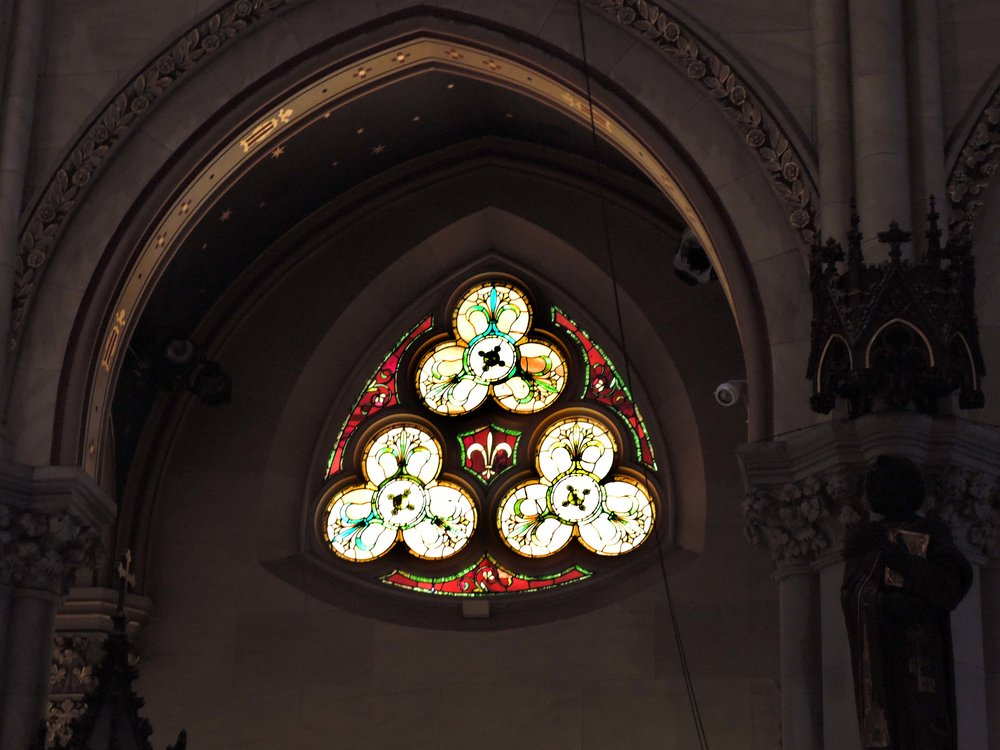 The window in the aisle over the entrance to the baptistery: trefoils and a fleur-de-lis
