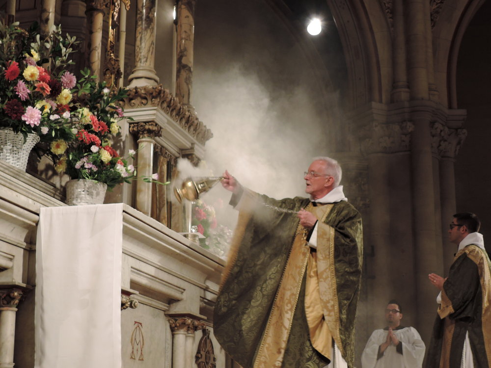 Father Jim Pace censes the altar last Sunday.
