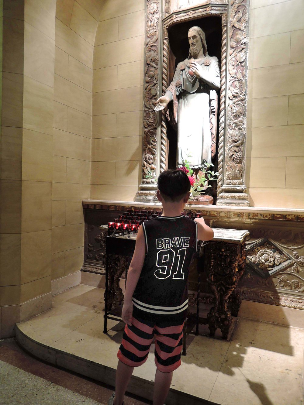 A young visitor lights a candle at the Sacred Heart Shrine.