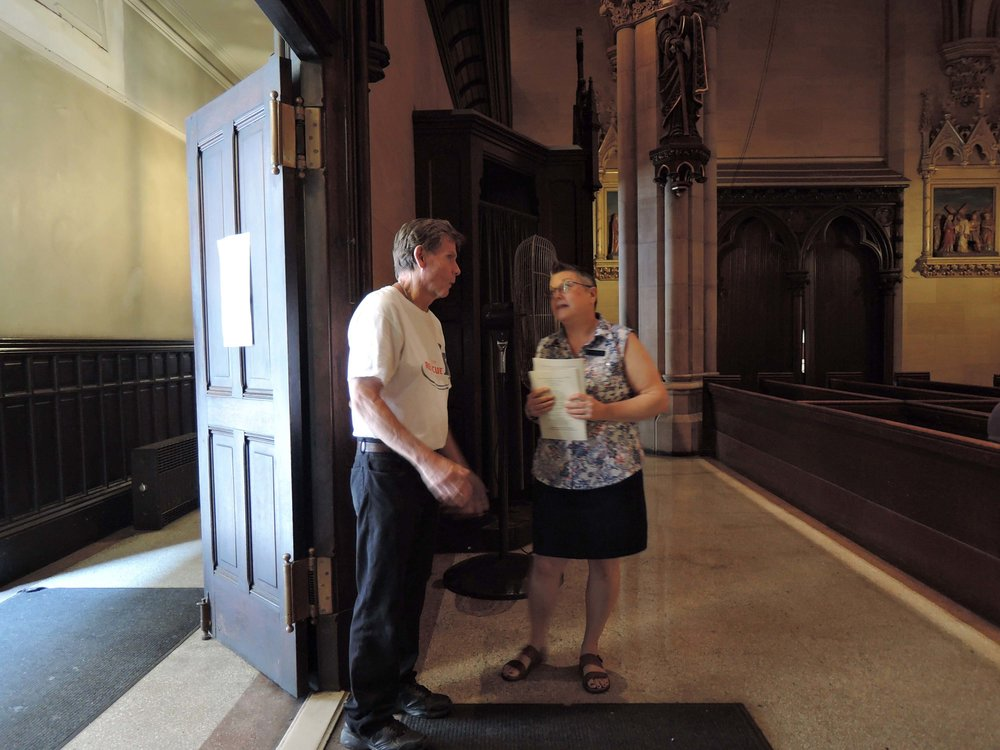 Usher Mary Robison chats with fellow parishioner Guy Strobel.