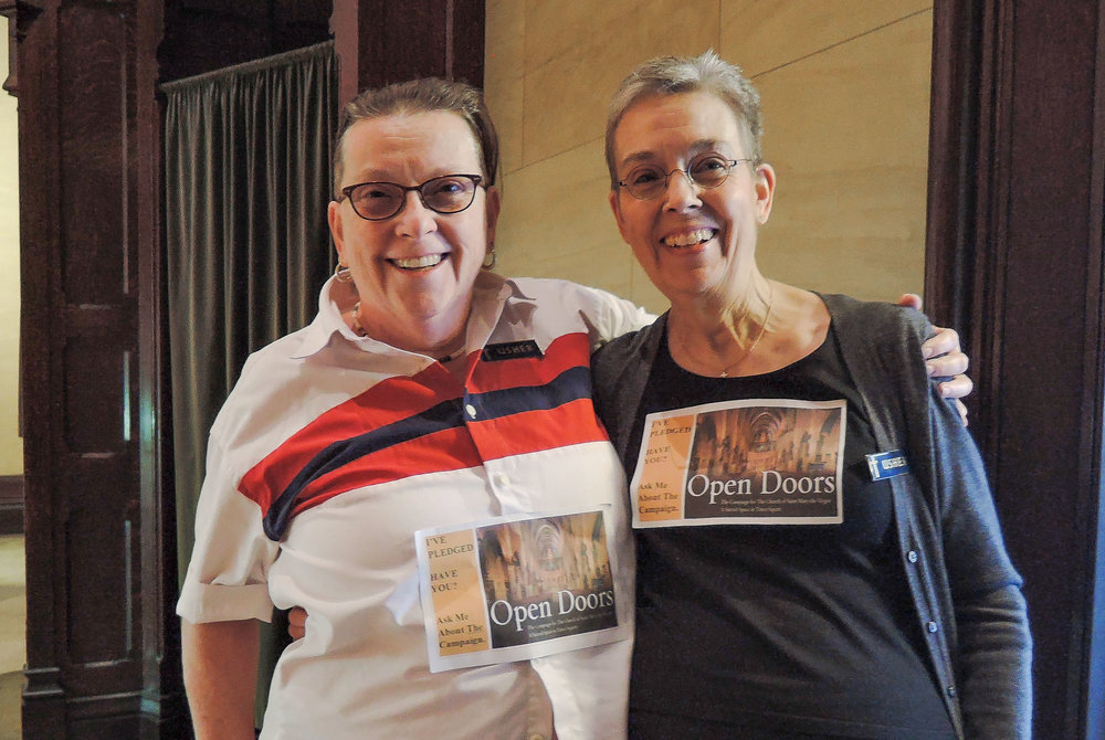 Ushers Pat Rheinhold (L) and MaryJane Boland wore signs to advertise the Open Doors Capital Campaign.