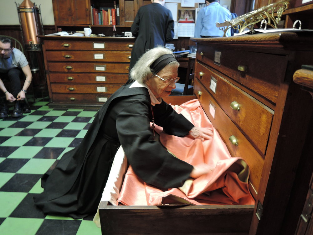 Sister Laura Katharine puts the rose vestments away at the end of Laetare Sunday.  Photo: Sister Monica Clare, C.S.J.B.