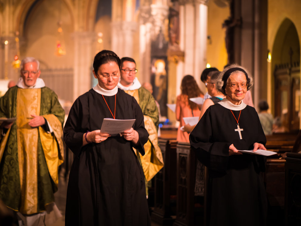 The ushers hand programs to those in the retiring procession so that they can join in the singing of the final hymn in the narthex.  Photo by Ricardo Gomez