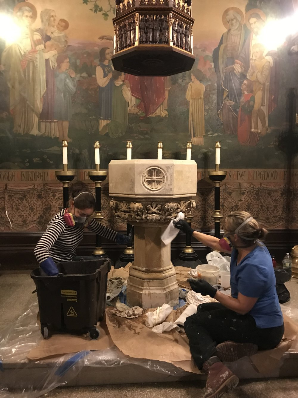 Conservators carefully remove layers of paint from the baptismal font.  Photo by S. Gerth