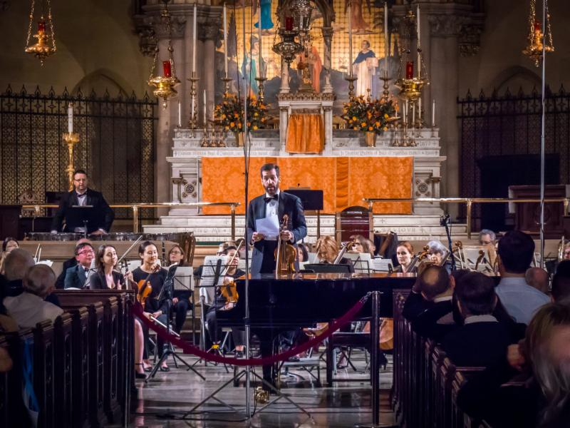 NYRO violist and emcee Phil Catelinet warms up the crowd before NYRO's final concert last season. Parishioner and NYRO cellist, Grace Mudd, at right.  Photo by Ricardo Gomez