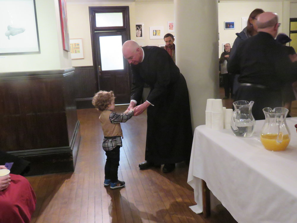 The Rector peels a clementine for a young member of the parish.   Photo by Br. Damien Joseph, SSF