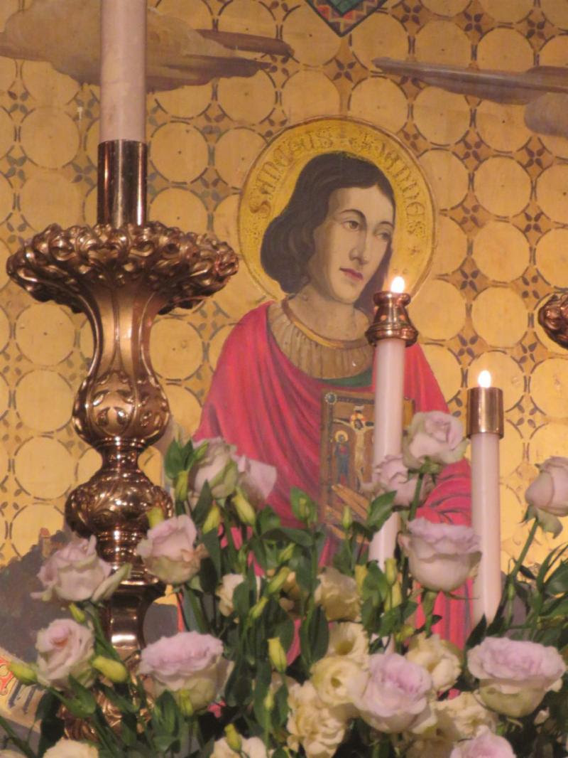 Saint John, viewed through candles and flowers on the high altar, in the high-altar reredos painting by Valentine d'Ogries (1922).  Photo: Br. Damien Joseph SSF
