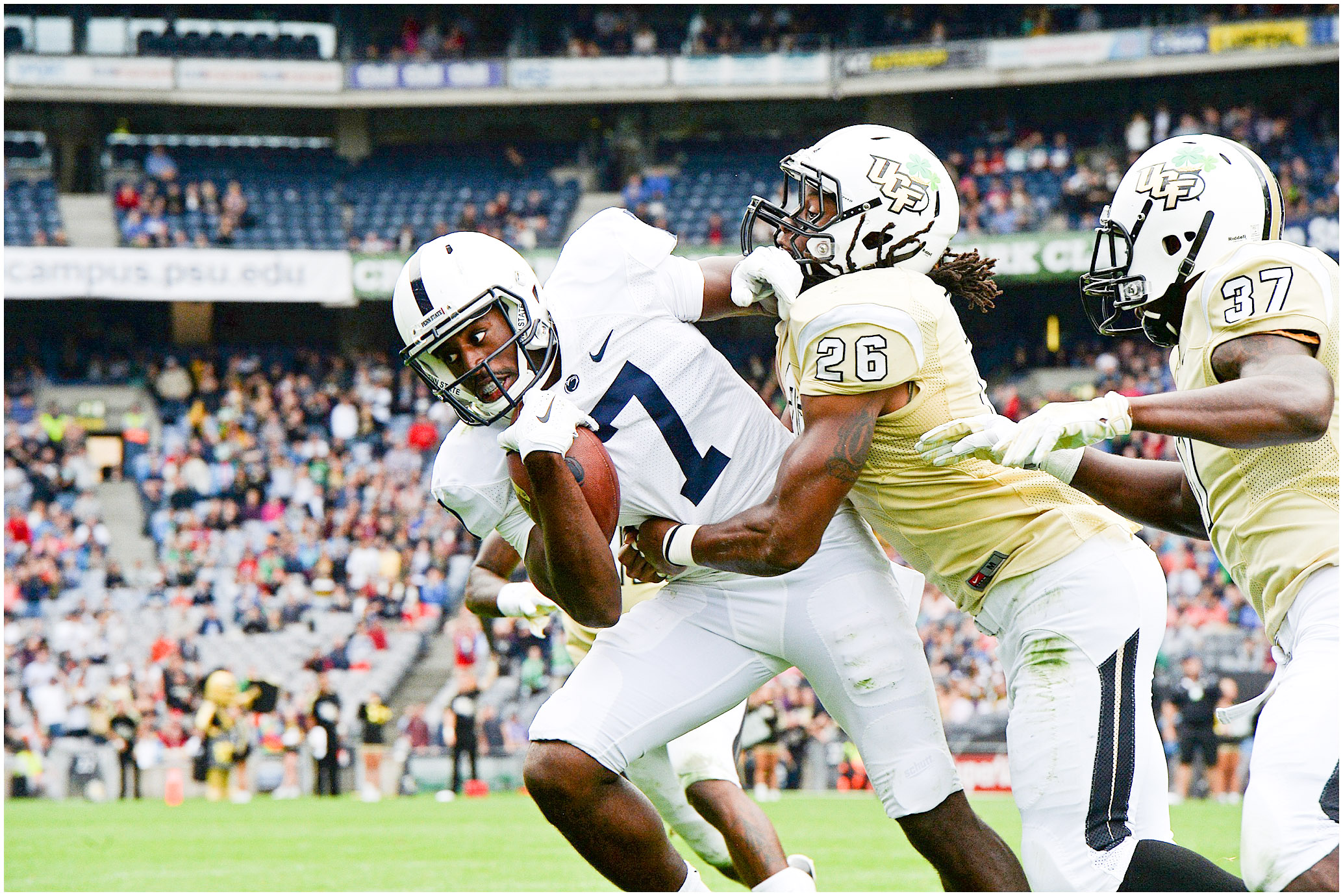 Penn State Nittany Lions wide receiver Geno Lewis (7) is tackled by UCF Knights defensive back Clayton Geathers (26) during the second half of the Croke Park Classic in Dublin, Ireland, on Saturday, Aug. 30, 2014. Penn State defeated Central Florida 26-24. Photo by Hannah Byrne