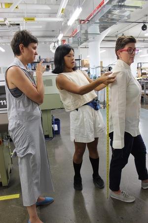 Maya and Tara making adjustments to the sleeve length and shoulder width