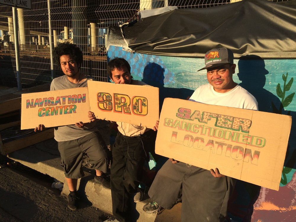 Box City encampment residents (7th Street at Mission Bay) holding up signs with transition goals (Fall 2016)