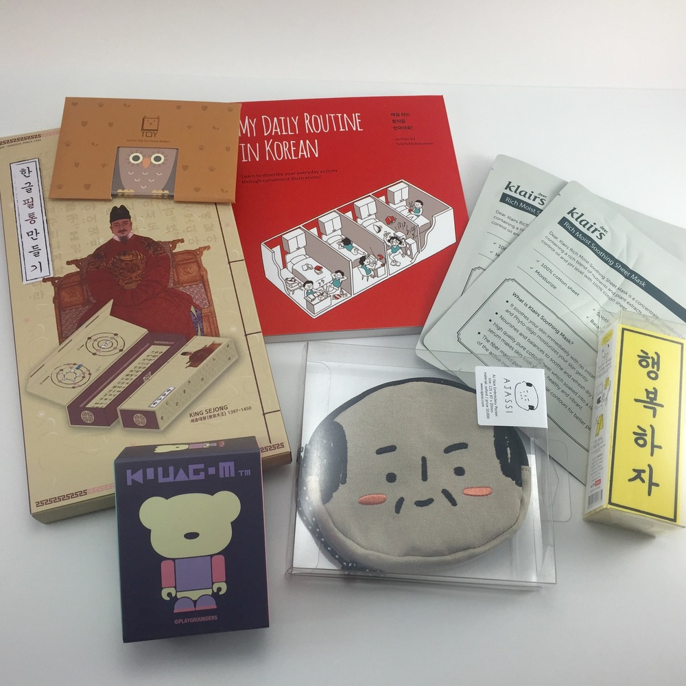 """For non-noms, we got tons of fun stuff! There's a do-it-yourself pencil case, an L-TOY (which is a cubed cardboard figure you put together - this one's an owl), a Kuuagom vinyl toy, a booklet of Korean phrases - """"MY Daily Routie in Korean"""", an AJASSI pouch, face masks, and a signboard that says """"Be Happy"""".."""