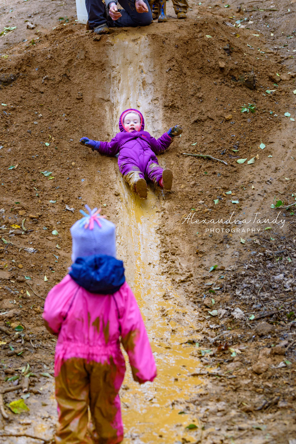 Alexandra-Tandy-Photography-two-toddler-girls-playing-on-mud-slide-at-forest-school.jpg