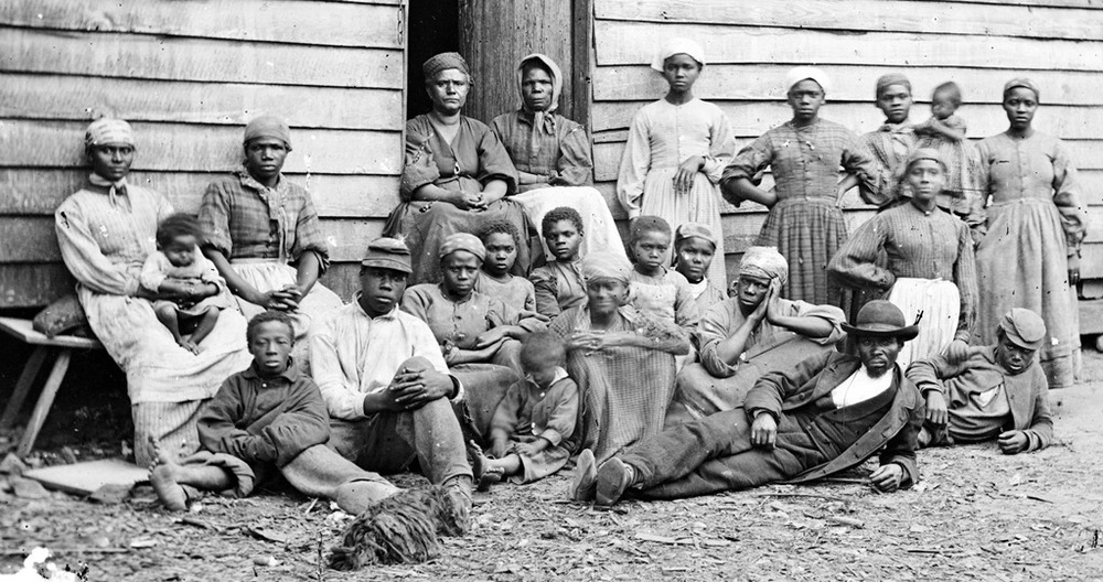 a-group-of-slaves-including-men-women-and-children-gathered-outside-a-building-at-the-Foller-Pla.jpg