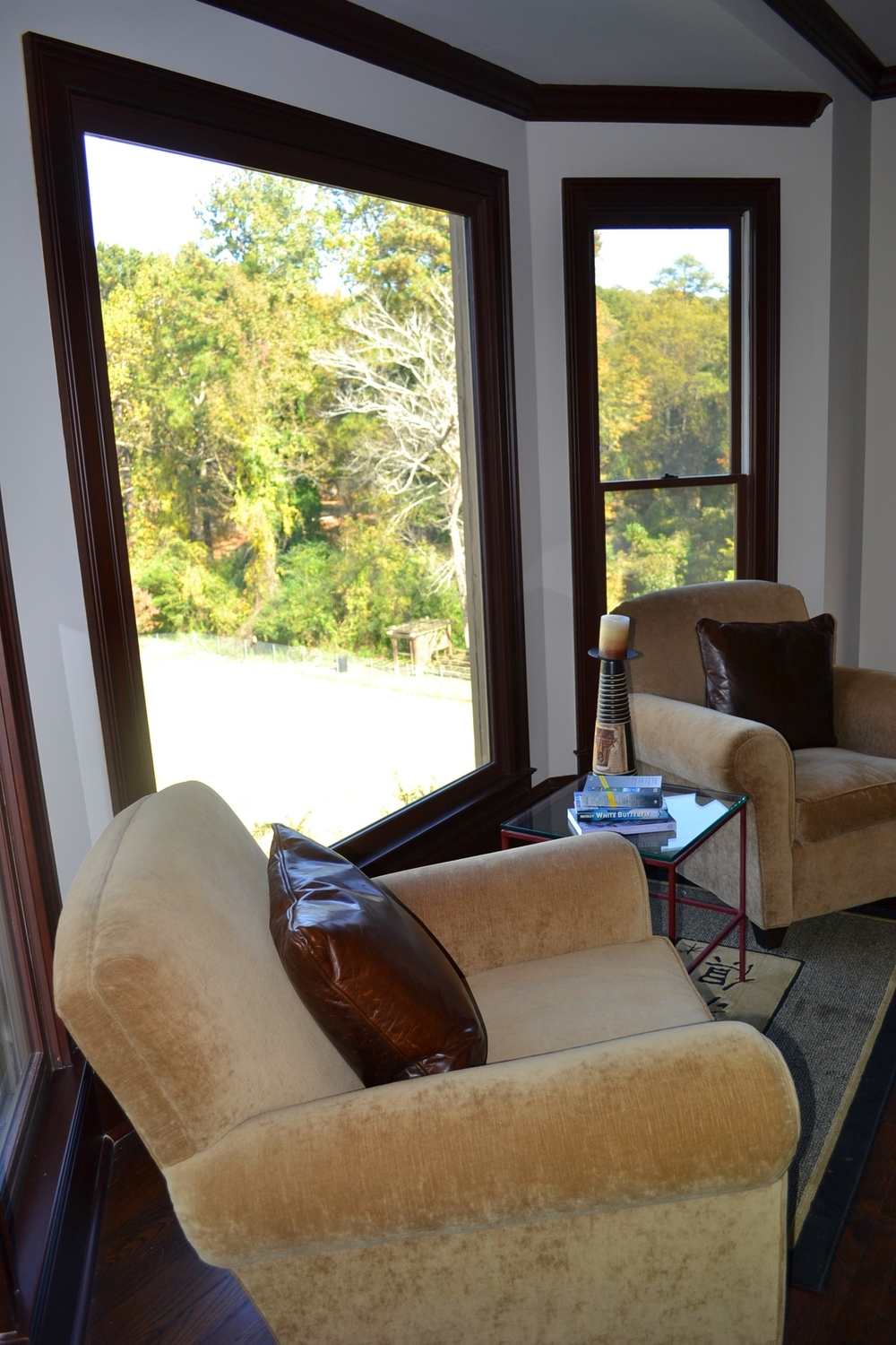Comfy club chairs in bay window overlooking park