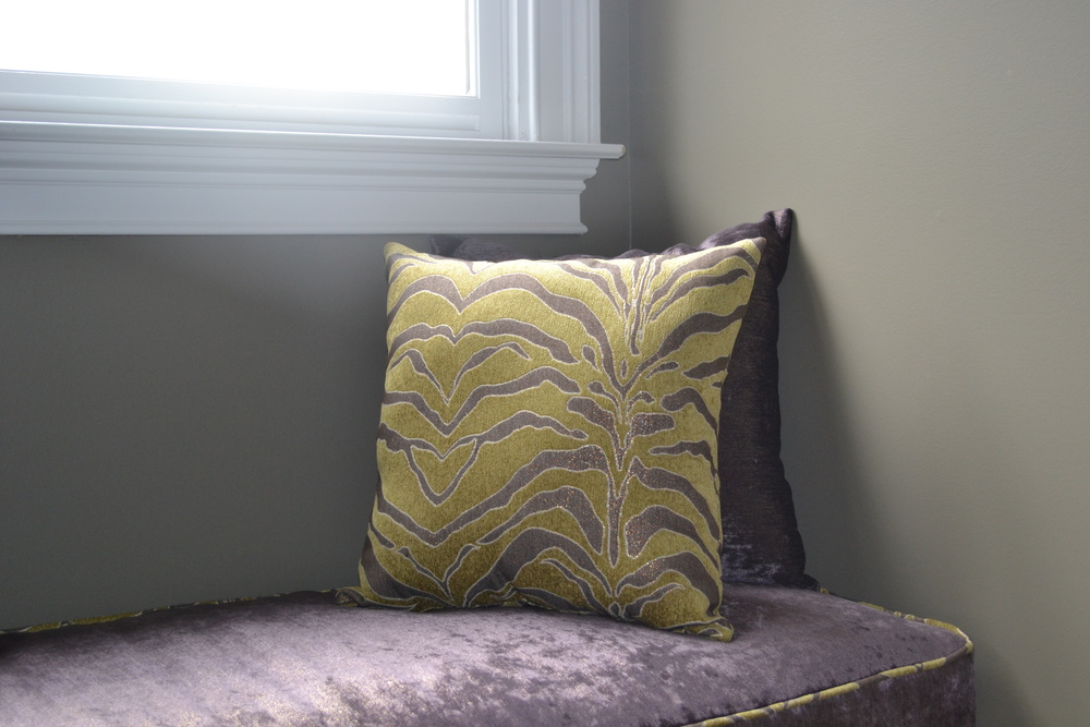 Chartreuse green and purple accent pillows flank window seat.