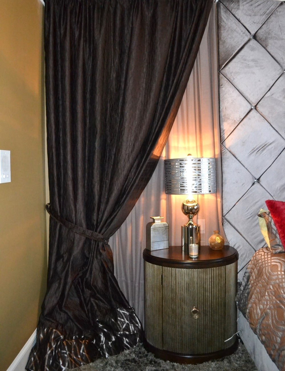 Custom drapery detail with chocolate and champagne drapery wall flanking beautiful demilune nightstands with decorative handle