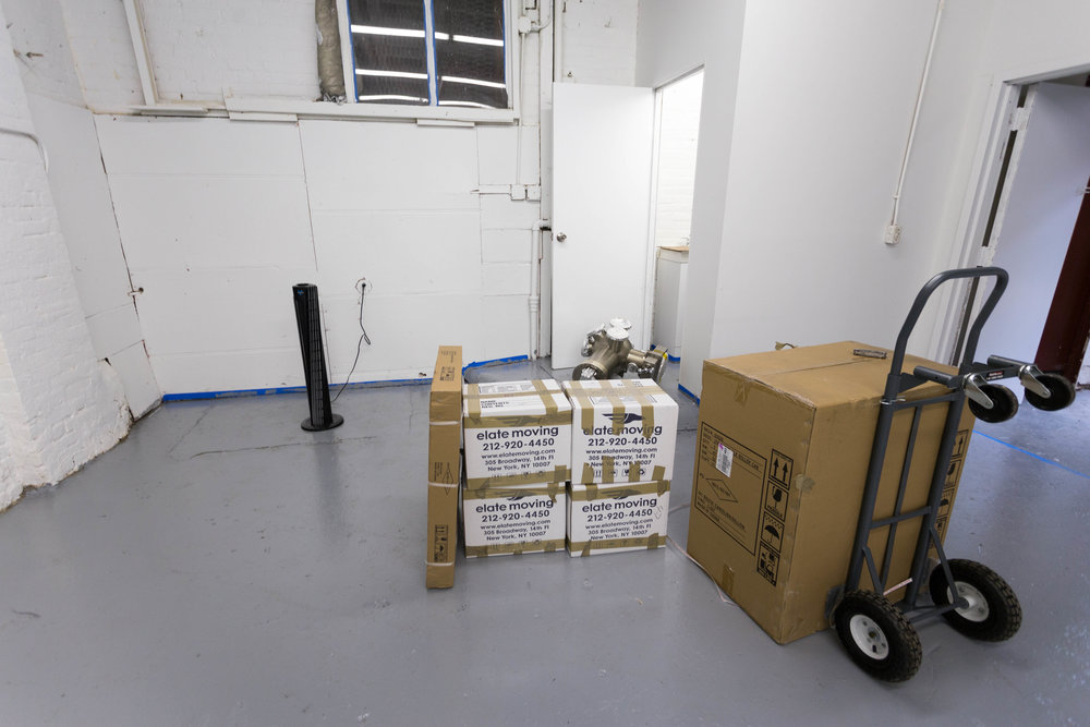 Some boxes and high vacuum equipment are being rolled in.