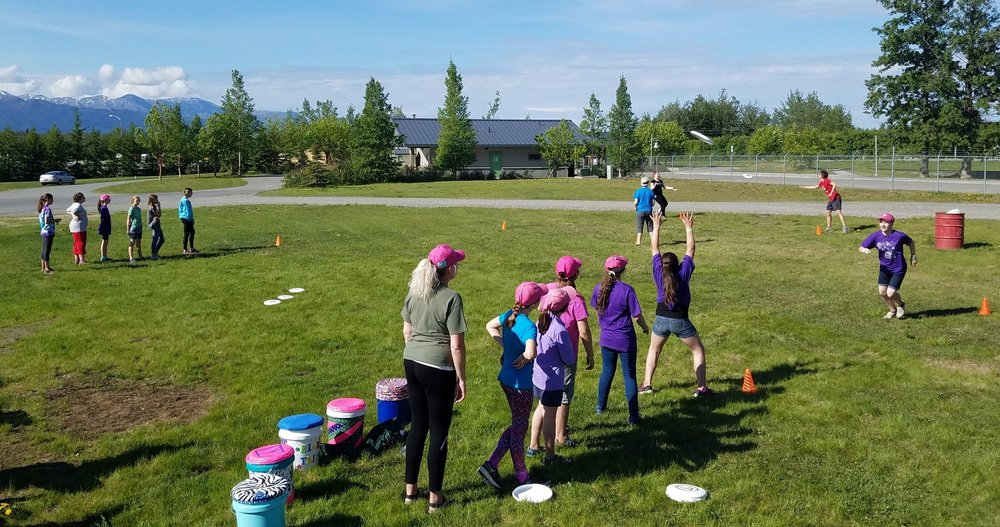 Leaders and girl scouts participated in a throwing relay to practice running & catching, stopping with the disc and throwing to space before playing a full game.
