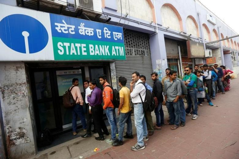 Indian citizens wait in line to use an ATM. (Photo via Reuters)