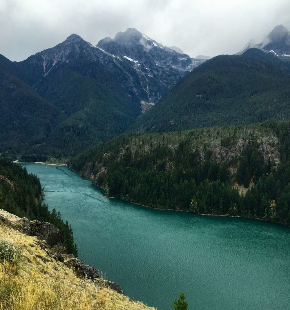 A grand view from Diablo Lake Overview, glaciers visible near tops of the mountain peaks, photo by Derek Wright.