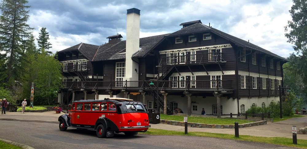 "Lake McDonald lodge with old-school ""jammer"" parked in front."