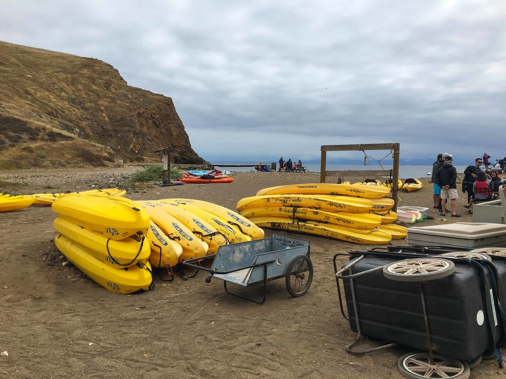 Sea kyacks awaiting bold trips with the Santa Barbara Adventure Company, on Santa Cruz Island. Photo by Derek Wright.