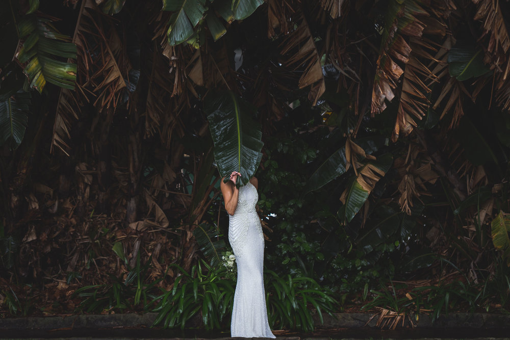 Bride holding palm leaf over her face. Quirky bridal photo. Chiswick restaurant wedding. Sydney