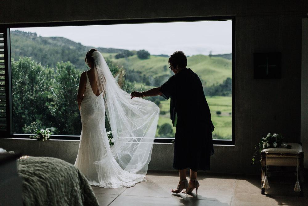Mother of the bride dressing daughter. Coromandel Coast Wedding. New Zealand Photographer