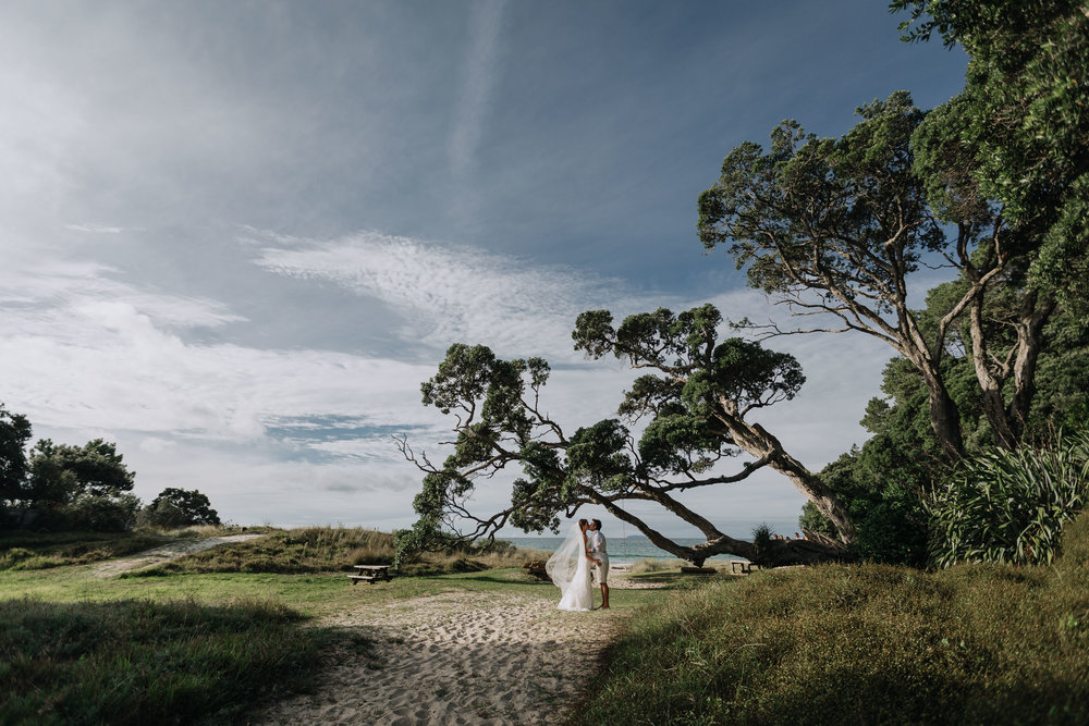 Bride and groom under a tree. Natural, relaxed wedding photography. Coromandel Coast wedding photography
