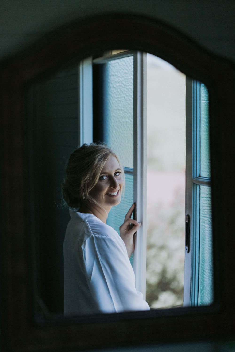 Smiling bride in the window. Natural, relaxed wedding photography Kiama