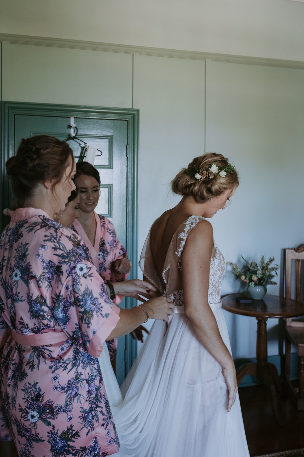 Bridesmaid fitting wedding dress on bride. Candid wedding photography on the South Coast