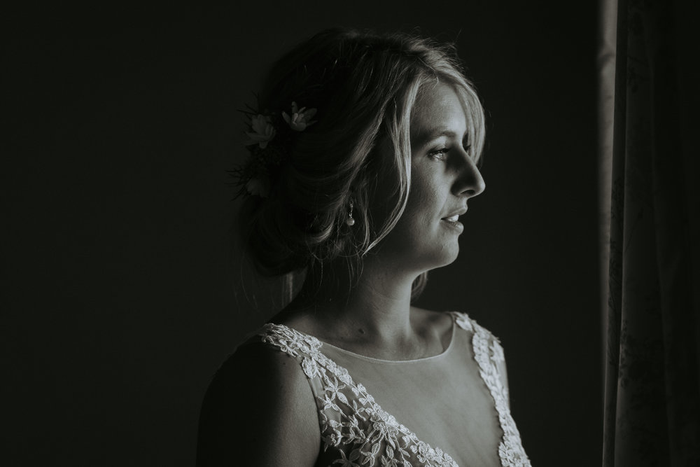 Black and white photo of bride in window. Natural wedding photography on the South Coast