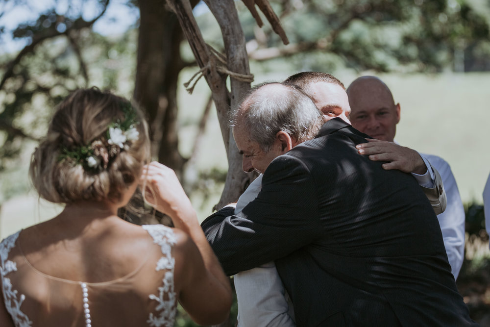 Father of the bride hugging groom photo. Natural wedding photography