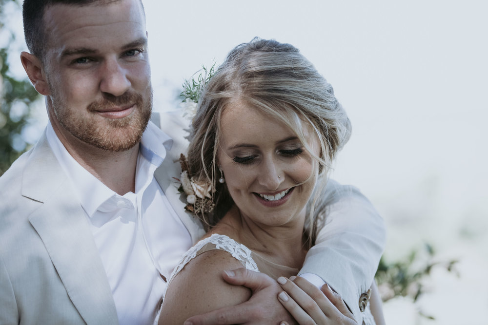 Smiling groom hugging bride photo. South Coast wedding photography.