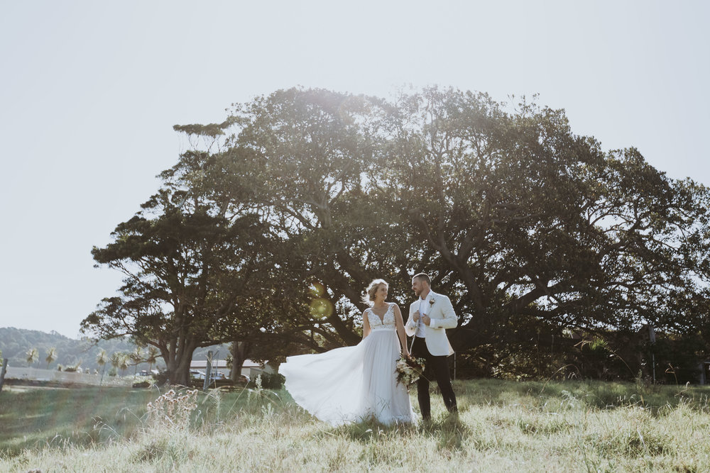 Bush Bank wedding Kiama. Bride and groom walking down paddock. Natural, relaxed wedding photography