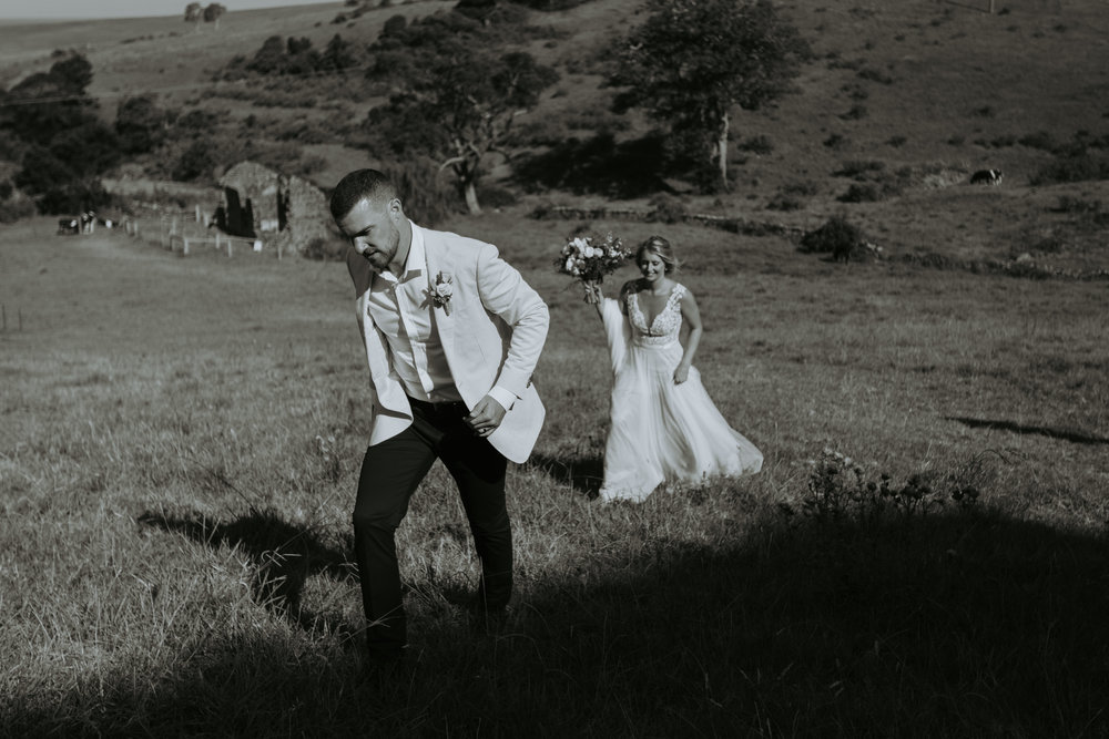 Bride chasing groom through paddock photo. Natural relaxed wedding photography. South coast wedding photographer.