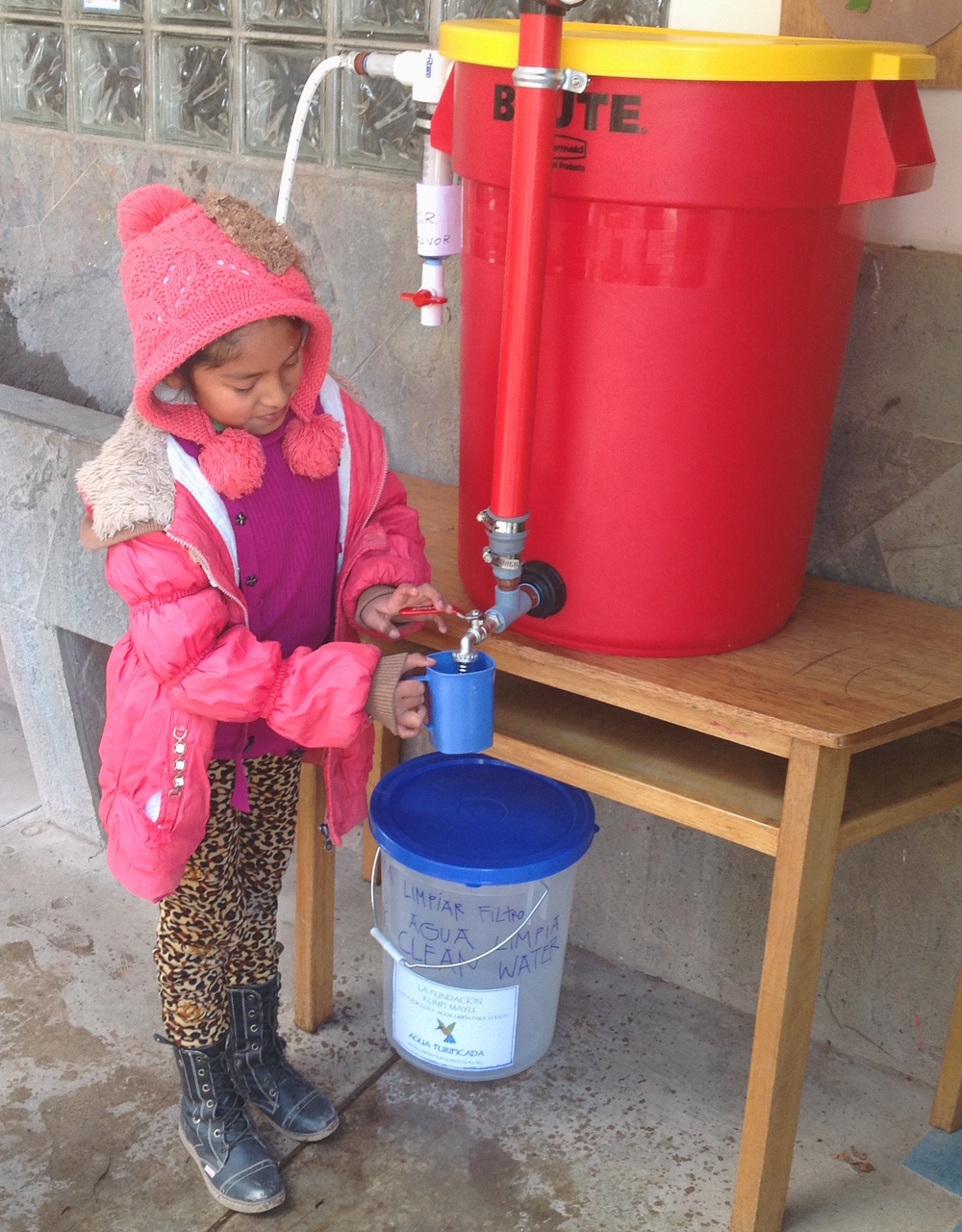 Littel girl getting water in school.jpg