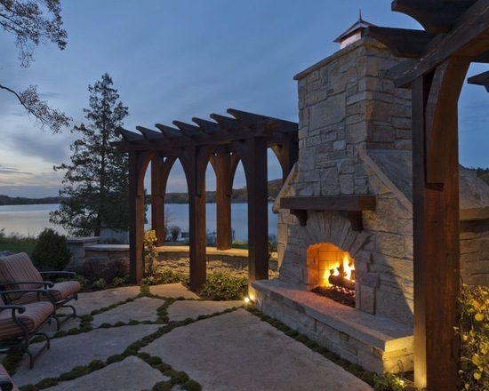 Custom stone outdoor fireplace by the lake with a custom wood pergola