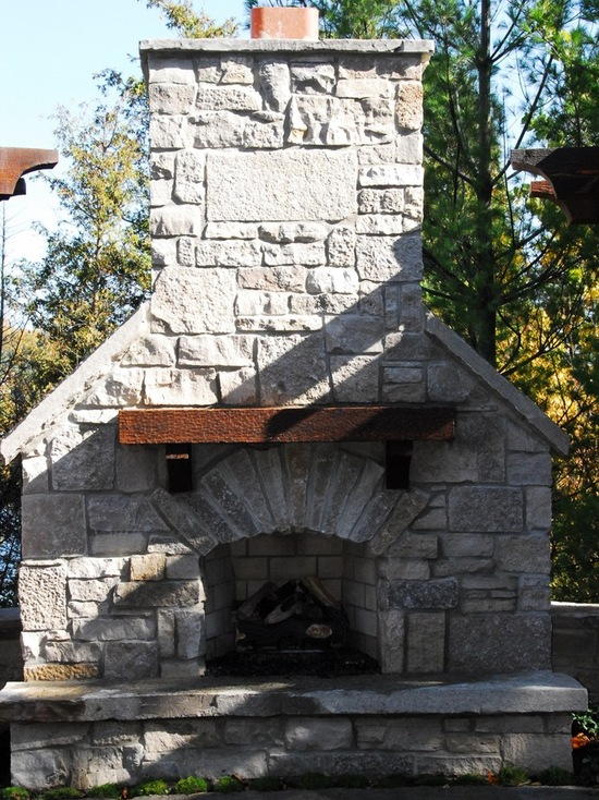 outfoor fireplace with chimney and wood mantle