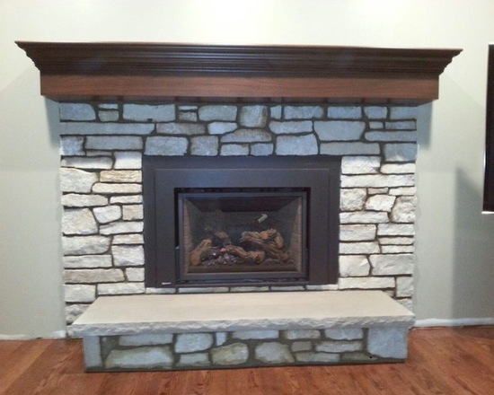 wooden mantle on top of natural stone fireplace
