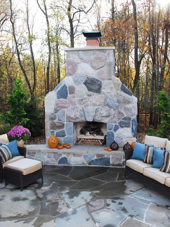Natural stone fireplace with pumpkins and outdoor furniture with pillows