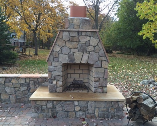 outdoor fireplace with chimney and stone wall