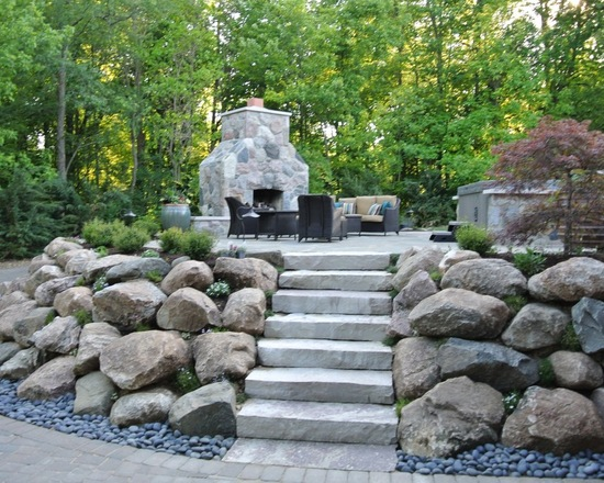 backyard steps and stone wall platform with a fireplace