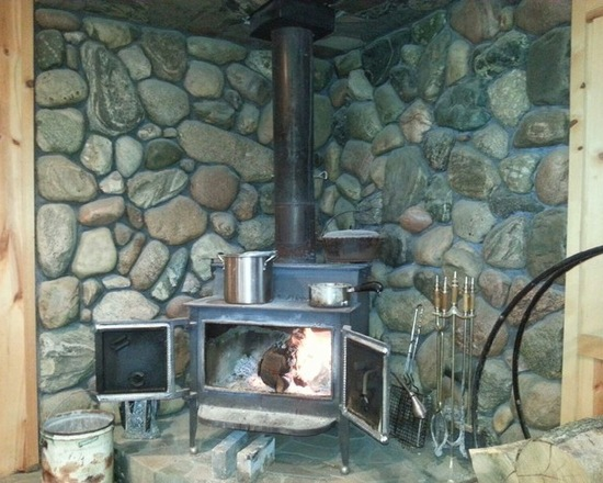 wood stove natural stone fireplace area