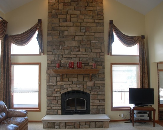 Fireplace between two large windows with curtains