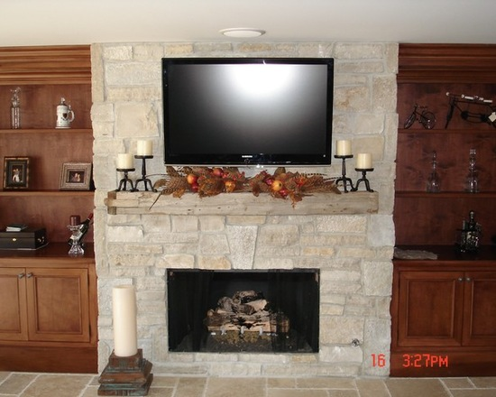 Fireplace with wooden cabinets on the sides and a tv mounted above the mantle