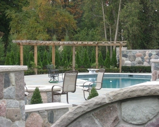 Wooden pergola overlooking pool with natural stone