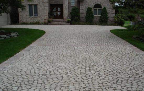 Large brick driveway in front of luxury home
