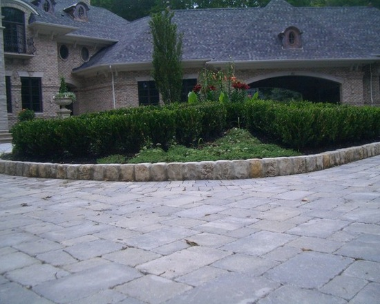 Brick driveway with brick curb and custom landscaping