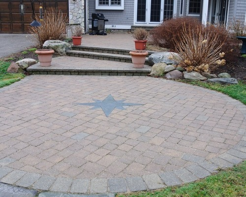 Circle bric paver with a compass rose in the middle in front of house